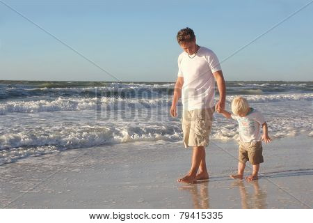 Young Child Holding Father's Hand While Walking In Ocean On Beach