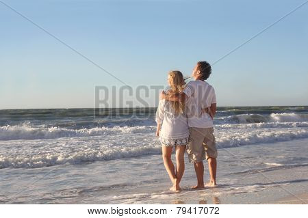Happy Couple Looking Out Over Ocean While Walking On Beach