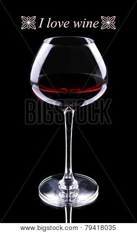 Wineglass with red wine and I love wine text, isolated on black