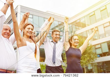 Many happy business people holding their arms up and cheering