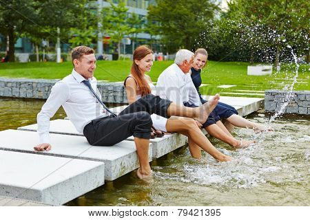 Happy business people splashing water in summer with their feet