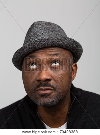 Black Man With Stubble Wearing A Hat Looking Up