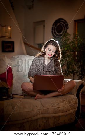 Beautiful young woman sitting on sofa working on laptop having a red gramophone near her, in boudoir