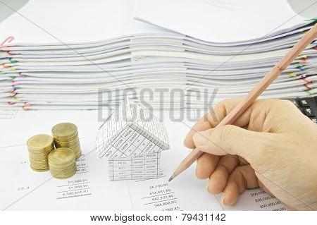 Man Checking Balance Sheet With Pencil