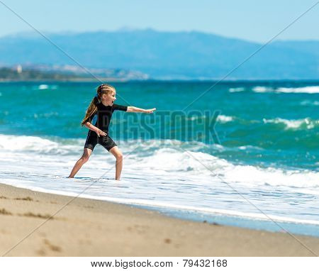 laughing  little girl playing in a wetsuit on the seashore