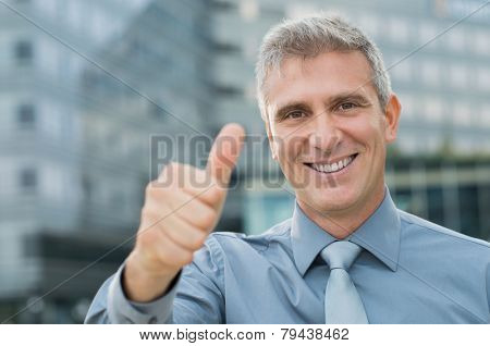 Closeup Of Smiling Businessman Showing Thumbs Up In Front Of The Building