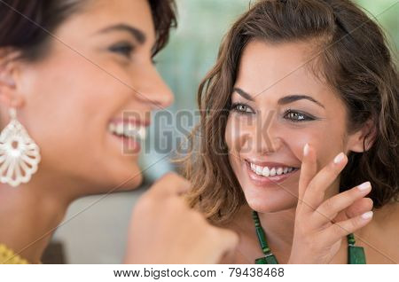 Close Up Of Two Young Woman Talking Each Other Aboutt A Gossip