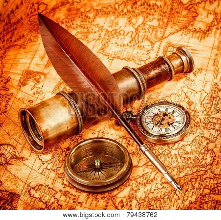 Vintage magnifying glass, compass, goose quill pen and spyglass lying on an old map in 1565.