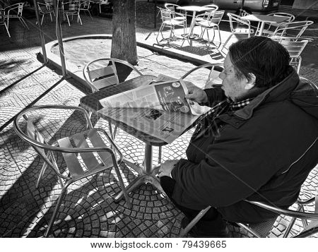SIRACUSA, ITALY - JANUARY 03 2015: a man with a cigar is sitting in an outdoor cafe and is reading a news paper. Shot in 2015