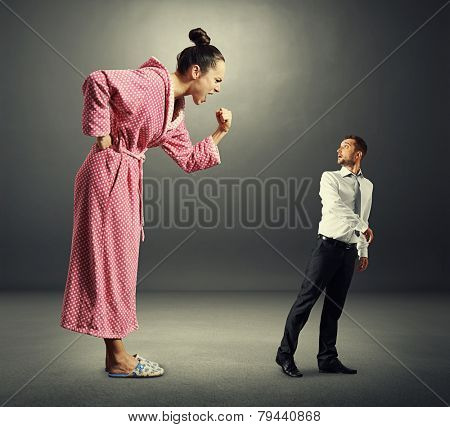 angry screaming woman shouting at small scared man. photo in the dark room