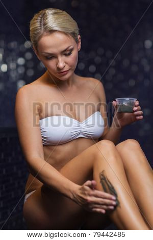 people, beauty, spa, healthy lifestyle and relaxation concept - beautiful young woman in swimsuit applying therapeutic mud