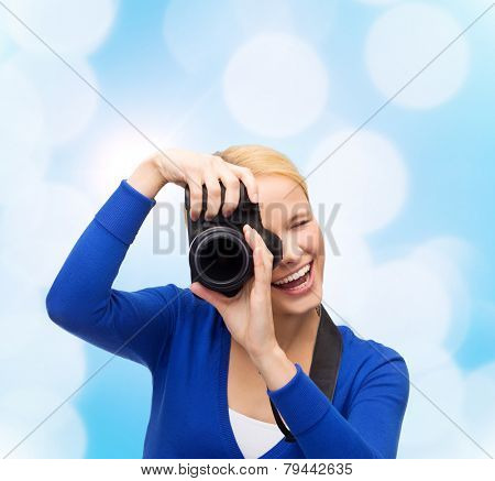 photography, technology and people concept - smiling young woman taking picture with digital camera over blue lights background