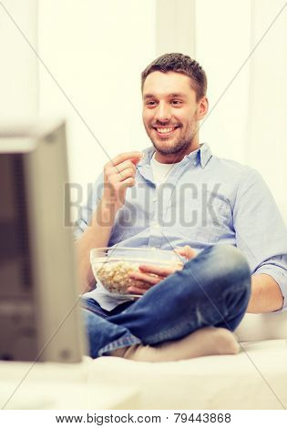 sports, food, happiness and people concept - smiling man with popcorn watching sports on tv and supporting team at home