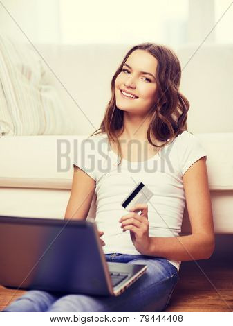 online shopping, banking and technology concept - smiling teenage girl with laptop computer and credit card at home