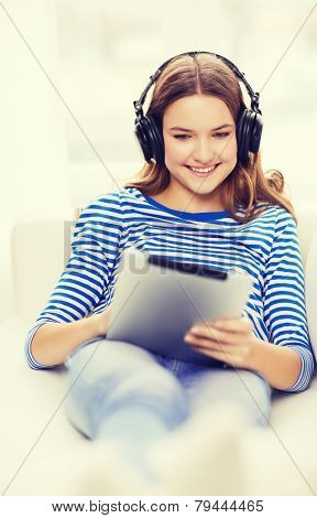 home, music, technology and internet concept - smiling teenage girl lying on the couch with tablet pc computer and headphones at home