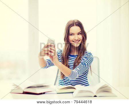 education, technology and home concept - happy smiling student girl with smartphone and books at home