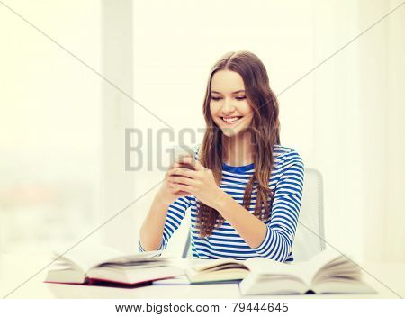 education, technology and home concept - happy smiling student girl with smartphone and books