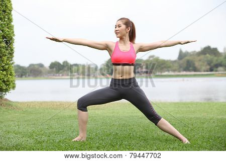 Yoga Virabhadrasana Ii Warrior Pose By Woman On Lawn,left Side