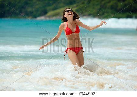 happy woman wearing sunglasses in water