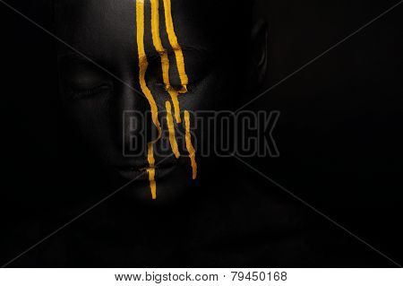 lady in black paint with yellow smudges