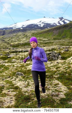 Running woman athlete exercising trail runner. Fit female sport fitness model training and jogging outdoors in beautiful mountain nature landscape by Snaefellsjokull, Snaefellsnes, Iceland.