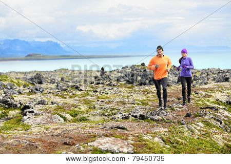 Exercise running sport. Runners on cross country trail run outdoors working out. Fit young fitness model man and asian woman training together outside in mountain nature on Snaefellsnes, Iceland.