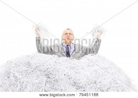 Desperate senior holding a bunch of shredded paper isolated on white background