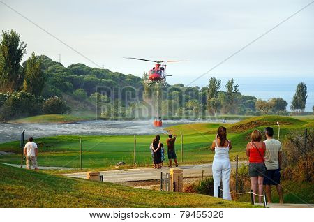 People watching helicopter collecting water.