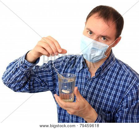 Man in a medical mask dissolves a pill