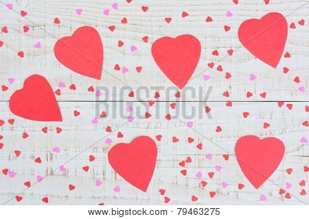 High angle shot of red and pink, large and mini, paper hearts for Valentine's Day scattered on a rustic whitewashed wood table. Horizontal format.
