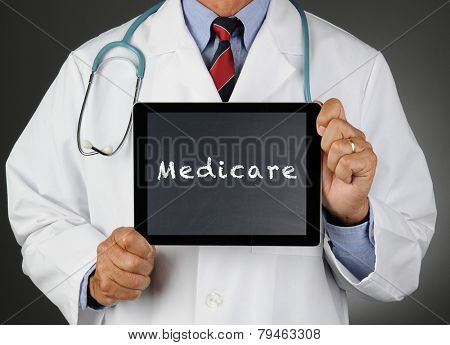 Closeup of a doctor holding a tablet computer with a chalkboard screen with the word Medicare. Man is unrecognizable.