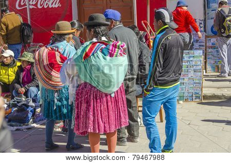 UYUNI, BOLIVIA, MAY 15, 2014:  Local women in traditional attire visit street market