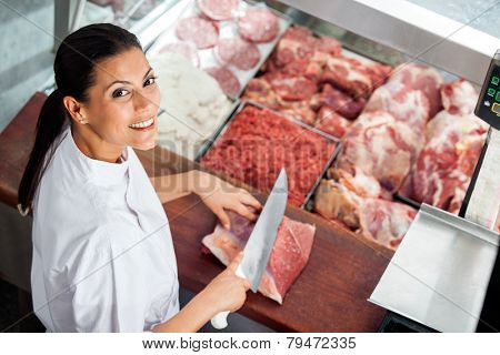 High angle portrait of happy female butcher cutting meat at butchery counter