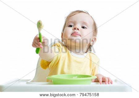 baby child sitting in chair and outstretching a spoon