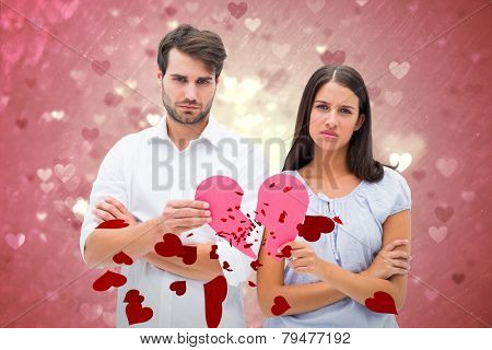 Upset couple holding two halves of broken heart against valentines heart design