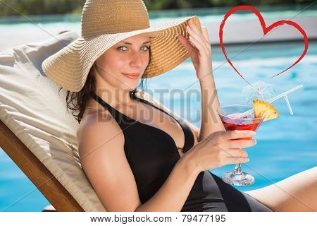 Beautiful woman holding drink by swimming pool against heart