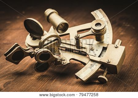 old bronze sextant on the wooden table