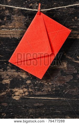Red  envelop  hanging on the clothesline. On old wood background