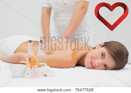 Attractive young woman receiving back massage at spa center against heart