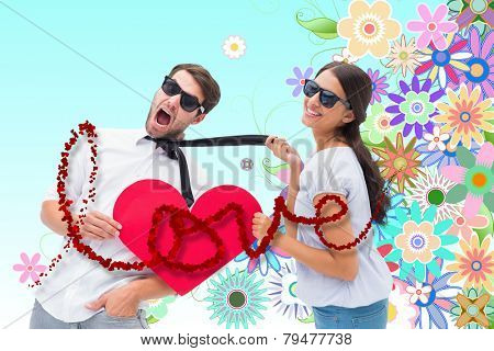 Brunette pulling her boyfriend by the tie holding heart against digitally generated girly floral design
