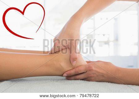 Woman receiving leg massage at spa center against heart
