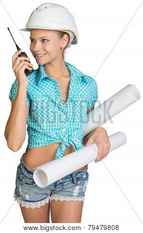 Beautiful girl in white helmet, shorts with shirt holding scrolls drawings and talking on walkie-tal