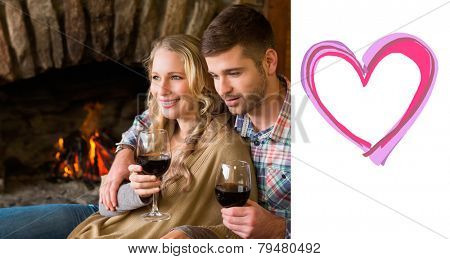Couple with wineglasses in front of lit fireplace against heart