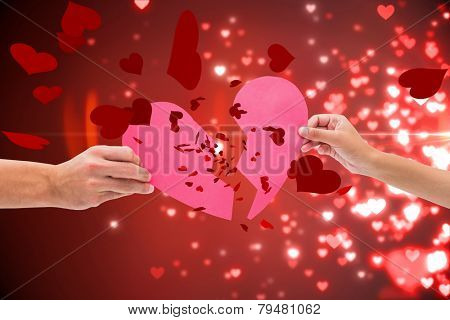 Hands holding two halves of broken heart against valentines heart design