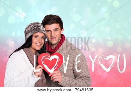 Young couple smiling holding red heart against blue and pink light spot design