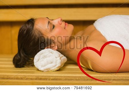Peaceful brunette relaxing in a sauna against heart