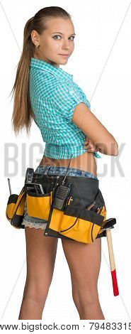 Pretty girl in shorts, shirt and tool belt with tools. Rear view