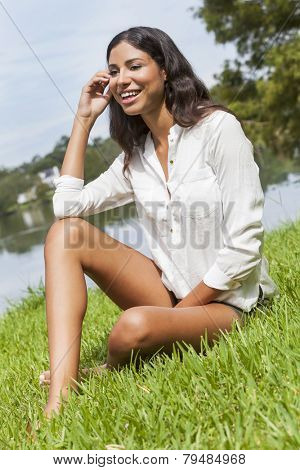 A sexy happy young Latina Hispanic brunette woman or girl wearing shorts laughing sitting on the grass by a lake on a sunny summer day