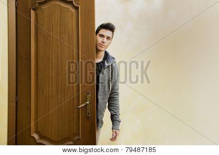 Handsome young man behind open door