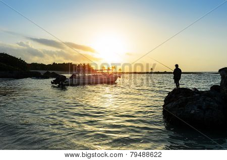 Man Fishing In The Caribbean Sea At Sunrise